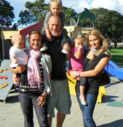 Picture of a host family and an Au Pair New Zealand au pair. Mum, dad and au pair are each carrying one child on their arms. Group photo.